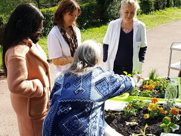Roxandra arrose son jardin thérapeutique à l'hôpital Sainte-Périne 2019
